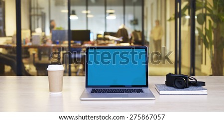 a laptop computer with blue screen, together with a camera and a cup of coffee on desk in a small stylish office. - stock photo