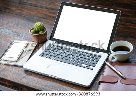 A laptop with white blank screen on the wooden desk table. - stock photo