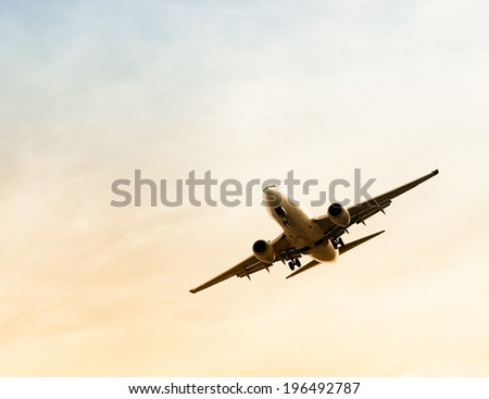 A large airplane at a forty-five degree angle in a pale yellow and blue sky. - stock photo