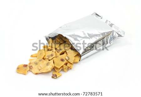 A large amount of peanut brittle candy spilling from a metallic bag onto a white background. - stock photo