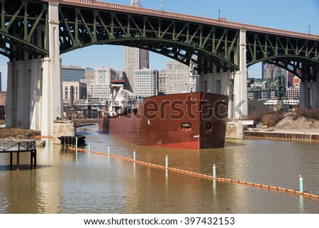 A large articulated tugboat and barge transporting taconite pellets to a local steel mill sails under the Hope Memorial Bridge upbound on the Cuyahoga River in Cleveland, Ohio  - stock photo