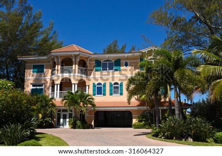 A Large Beach House with Beautiful Landscaping on the Florida Coast - stock photo