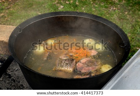 a large black vat with fish soup outdoors - stock photo