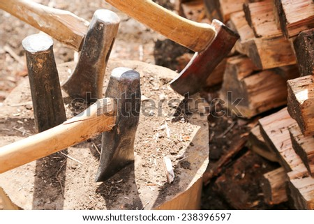 A large block of wood holds several axes for wood splitting during spring clean up weekend at the cottage - stock photo