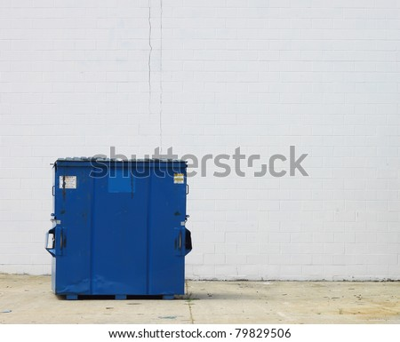 A large blue trash dumpster for waste and refuse disposal in the back of a Business against a cinder block wall with room for your text. - stock photo