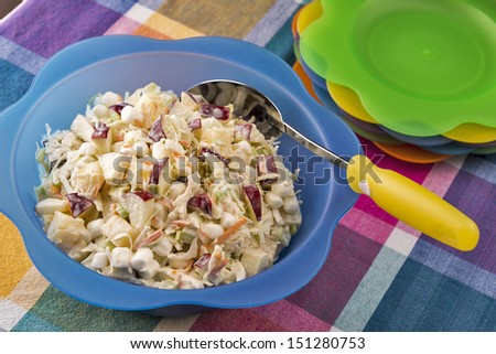 A large bright bowl of coleslaw made with apples, marshmallows and pineapple is ready for a summer picnic. - stock photo