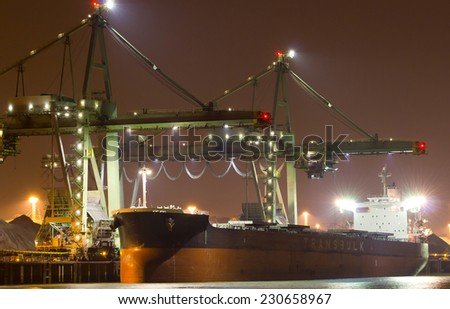 A large bulk carrier supplying iron-ore in a harbor - stock photo