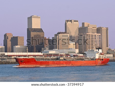 A large cargo ship in the Mississippi river sails past the New Orleans skyline - stock photo