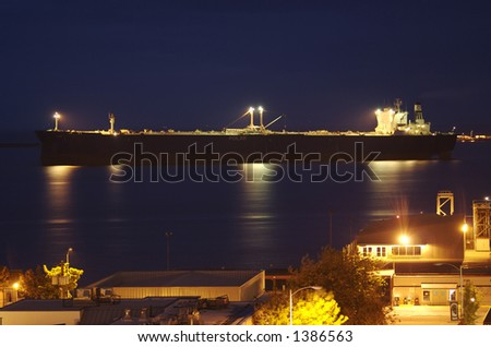 A large cargo ship pulls into port as a warm summer night sets in on a small coastal city. - stock photo