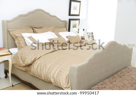 a large comfortable bedroom with a bed and lots of pillows - stock photo