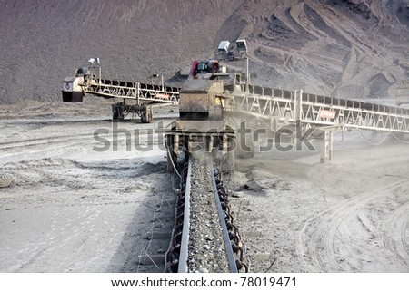a large conveyor belt carrying golden ore - stock photo