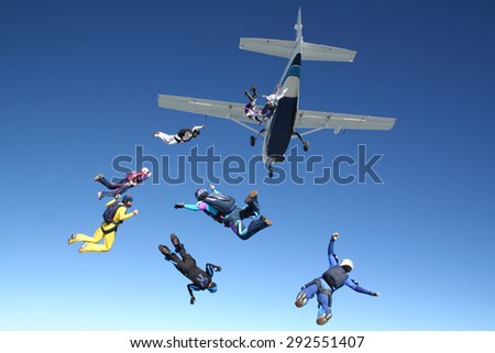 A large group of friends having fun practicing Skydiving in a beautiful day of summer sun. - stock photo