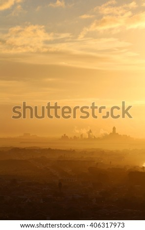 A large industrial plant billows smoke and pollution into the air against an orange sky as the sun rises. - stock photo