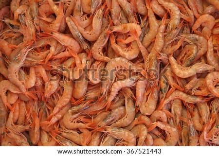 A large pile of fresh shrimp at a fish market.  - stock photo