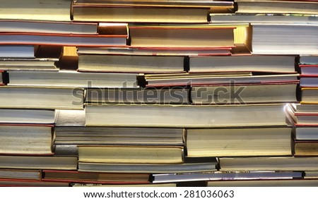A large pile of old books stacked like a wall - stock photo