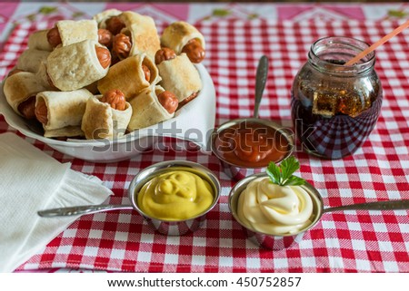A large plate with a mini hot dogs homemade (hot dogs in pastry) with ketchup, mustard, mayonnaise and cola in a glass jar on a plaid background - stock photo