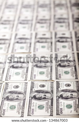 A large quantity of 100 US$ money notes lined up in rows. Very shallow depth of field. - stock photo