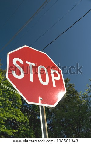 A large red stop sign shines brightly in the sunlight. - stock photo