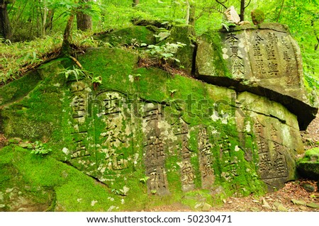 A large rock face covered in ancient text engravings and moss. Taken at a South Korean Temple. - stock photo