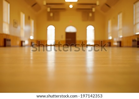 A large room with hardwood floors and a big wood door. - stock photo