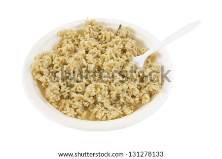 A large serving of risotto rice with asparagus on a paper plate with a white plastic fork. - stock photo