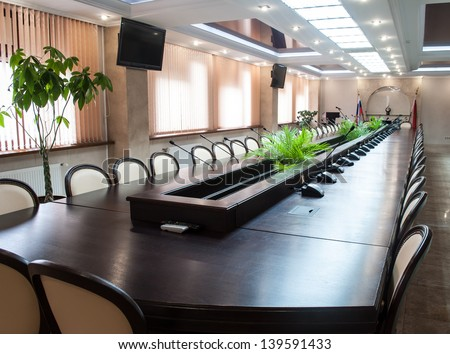 A large table and chairs in a modern conference room. - stock photo