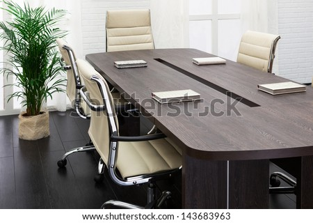 a large table and chairs in a modern conference room - stock photo