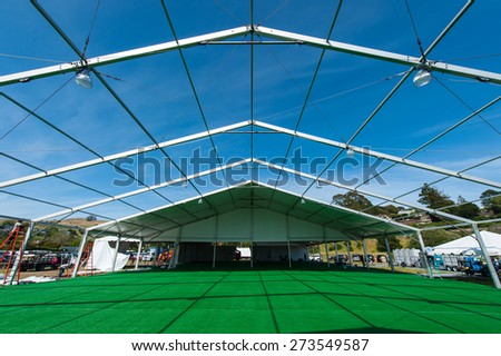 A large tent in a grassy field is being constructed for a party - stock photo