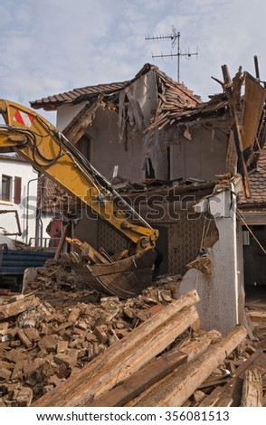 A large track hoe excavator tearing down an old house - stock photo