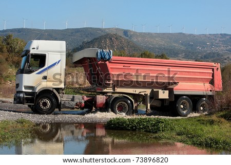 A large truck drives through a small river in the Spanish countryside - stock photo