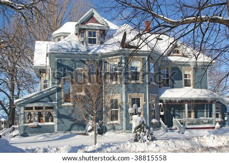 A large Victorian home covered with snow. - stock photo