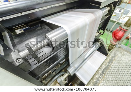 A large webset offset printing press running a long roll off paper over its rollers at high speed. - stock photo