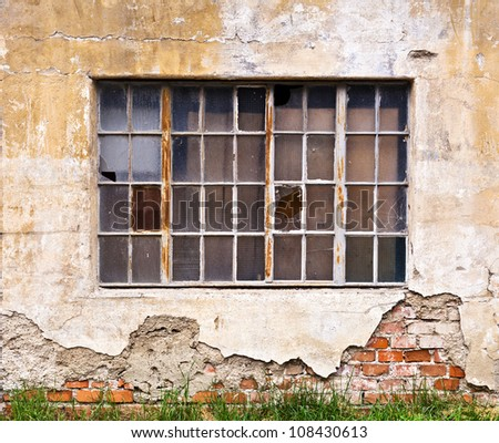 A large window with broken panes on the wall of a dilapidated old building - stock photo