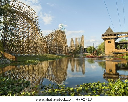 A large wooden roller coaster overlooks a lake at Great Adventure in New Jersey. - stock photo