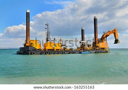 A large yellow excavator machine construct sea defencies on the beach - stock photo
