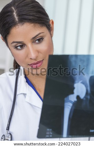 A Latina Hispanic female medical doctor surgeon looking at hip replacement x-ray in a hospital - stock photo