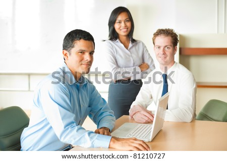 A latino businessman leads a diverse team of business people including an attractive Asian woman and caucasian male. - stock photo