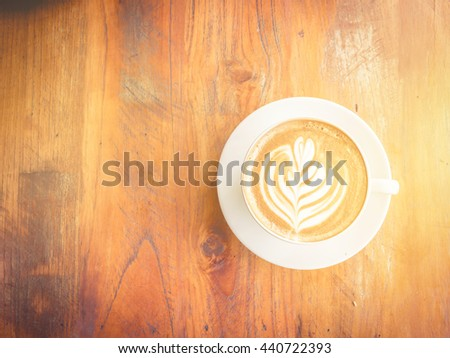 A Latte Coffee cup art on wooden desk. vintage effect. - stock photo