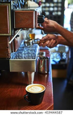 a latte sitting next to an espresso machine - stock photo