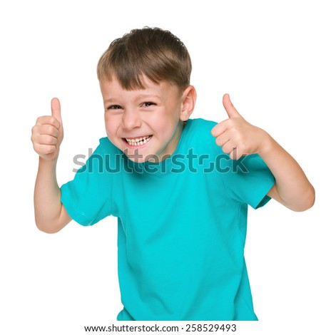 A laughing little boy holds his thumbs up against the white background - stock photo