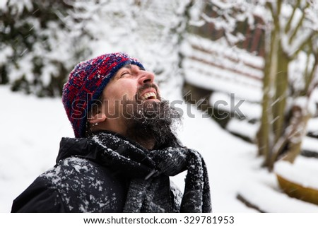 a laughing man in front of a snowy background - stock photo