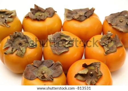 A layout of persimmons arranged in a triangle on a white surface and background - stock photo
