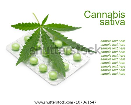 a leaf of marijuana (Cannabis sativa) on a blister with green drugs - stock photo