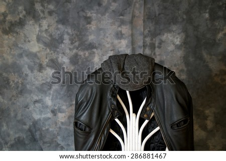 A leather motorcycle jacket hangs on the back of a chair with a tweed cap sitting on top. - stock photo