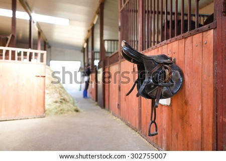 A leather saddles horse in a stable - stock photo