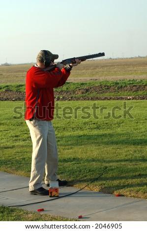 A left-handed shotgun shooter on the trap range - stock photo