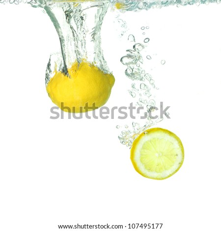 a lemon and a slice of lemon falling into clear water - stock photo