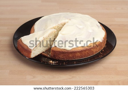 A lemon cake with icing with a cut slice half out - stock photo
