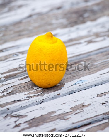 a lemon on wooden table with flaking paint slightly from above - stock photo