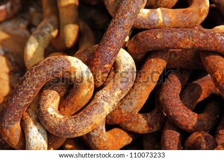 A length of coiled, rusty chain that lay abandoned on a beach. - stock photo